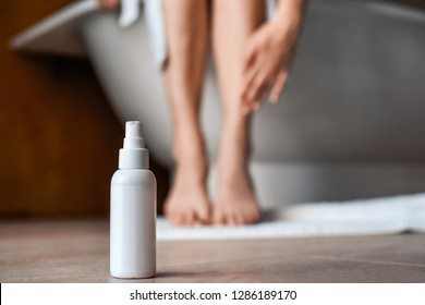 Body care. Young woman in the bathroom stroking her legs. Means against varicose veins and edema in the foreground.