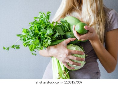 Woman's body closeup holding fresh green vegetables and fruits on gray background