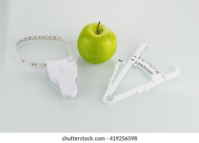 Body fat caliper, body measurement tape, and an apple