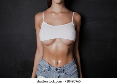 Body of a girl with big breasts with big breasts in a very short white tank top.