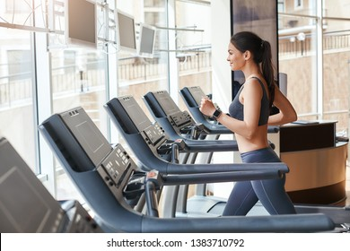Body improvement. Side view of young and beautiful woman in sportswear running on a treadmill at gym. Cardio workout.