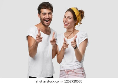 Body language concept. Positive young woman and man with joyful expressions, point at camera as if choosing you, smiles happily, dressed in white t shirt and headwear, pose together in studio
