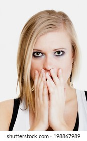 Body language and emotions. Surprised afraid blonde girl shocked young woman covering mouth with hand isolated on white.