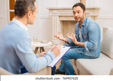 Body language. Experienced psychologist listening how striking nice man describing his situation looking at him and using body language