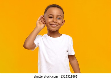 Body language, feelings and senses concept. Isolated view of cheerful dark skinned boy in white t-shirt smiling broadly and keeping hand at his ear while eavesdropping, overhearing, spying on someone