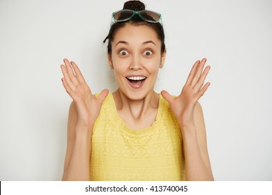 Body language. Human face expressions and emotions. Close up portrait of young brunette woman wearing casual yellow top and sunglasses on her head looking and gesturing in excitement and surprise.