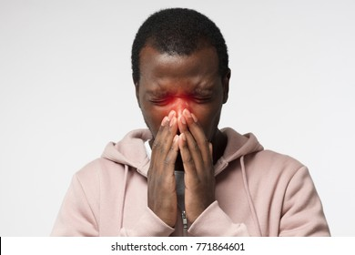 Body language. Sick young african man in pink hoodie covering face with hands; sneezing; isolated on gray background