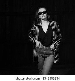 Body length interior portrait of stylish young female modelwearing grey jeans and striped blazer standing and posing in dark room. Vogue style. Studio shot