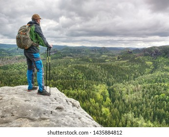 The body of man with a backpack and running shoes stands on top of a rock against the background rocky valley high in the mountains. The concept of tourism