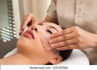 Body Massage on facial face of Mix Race Caucasian Asian woman, Therapist Spa body woman hands treatment on customer with Chakra Balancing massage scrub hot Jade stone effect inner emotion aesthetics