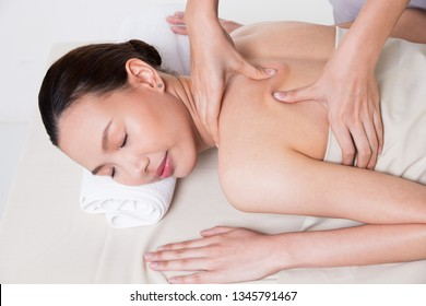 Body Massage on specific naked back of Asian woman by pressing fingers on pain or stress muscle point to release relax.  Therapist Spa body massage woman hands treatment on customer, isolated on white