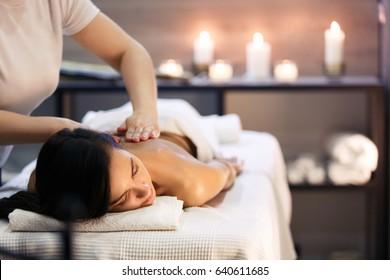 ロウソクと現代サロンでのボディーマッサージと温泉療法。ボディーケアのコンセプトマッサー手の接写