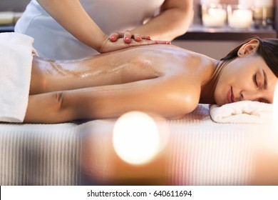 Body massage and spa treatment in modern salon with candles. Body care concept, masseur hands close up