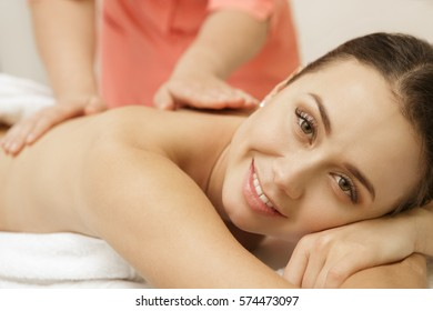 Body massage. Young beautiful woman smiling to the camera while getting a massage at the spa center body skin beauty wellness wellbeing recreation resort relaxation spa treatment occupation concept