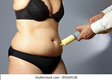 Body of a middle aged fat woman in underwear with man's hands holding a syringe with fat sucked out of the adipose tissue of her abdomen, liposuction or tummy tuck