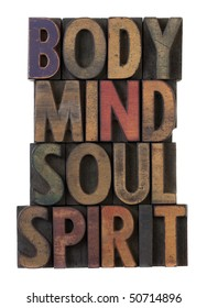 body, mind, soul, spirit in vintage wooden letterpress types, stained by ink in different colors, isolated on white