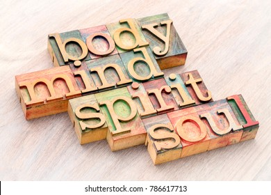 body, mind, spirit and soul word abstract in letterpress wood type against grained wood