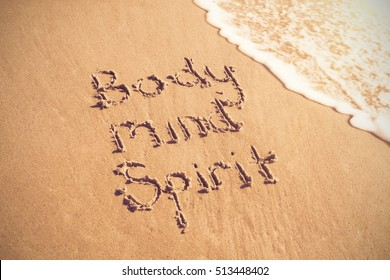 Body mind spirit text written on sand with surf at beach