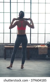 Body and mind workout in loft fitness studio. Seen from behind fitness woman with towel in loft gym