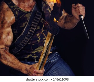 Body of muscular commando holding knife and torch