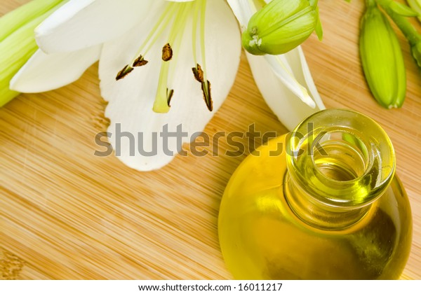 body oil and a beautiful white lily on wooden background