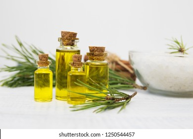 body oil in small jars on a background of pine branches, toned