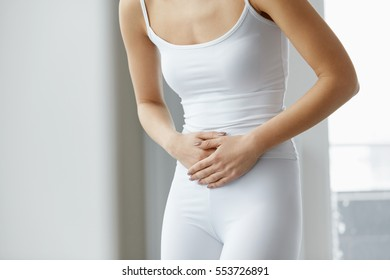 Body Pain. Closeup Of Beautiful Woman's Body Having Strong Abdominal Pain. Female Suffering From Painful Feeling In Stomach, Stomach Ache, Holding Hands On Belly. Health Issue Concept. High Resolution