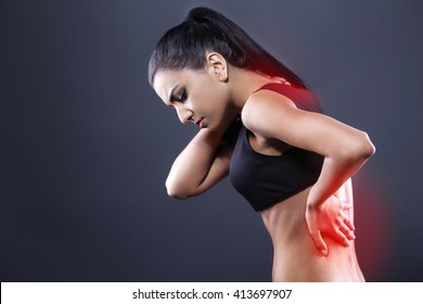 Body pain. Studio shot of beautiful young woman with dark brown hair. Woman suffering from backache. Red spot on back