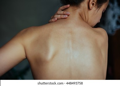Body pain. Studio shot of beautiful young woman with dark brown hair. Woman suffering from neck ache. Healthy lifestyle. Back and spine disease.