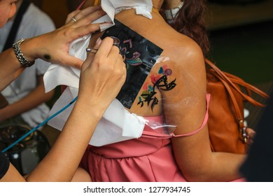 Body paint artist is painting pattern on the skin of a woman. At the street shop
