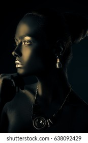 Body painting project. Portrait of a gorgeous young woman with perfect black skin and silver glitter lips wearing beautiful necklace and earrings. Cosmetics and make-up. Jewelry and bijouterie.