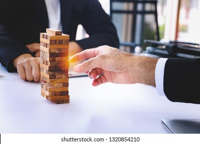 Body part Business engineers plays Jenga game and Orange ray. They are sitting in office and play game.Photo concept for engineering  and work.