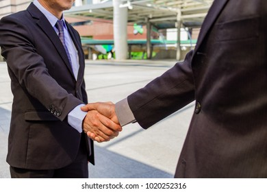 Body part business man handing a contract agreement and after a deal between business success.They are wear a suit and smile.They are happy beside stream in town.Photo concept  business and success.
