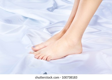 body part shot of beautiful healthy young woman's legs on silk cloth