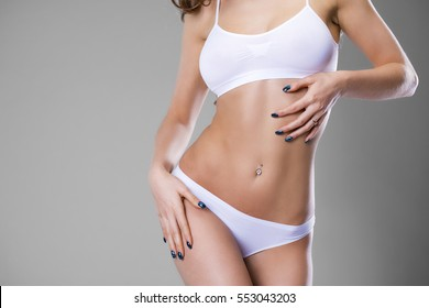 Body part white fitness underwear. Slim tanned woman's body. Isolated over gray background.