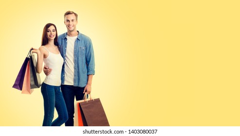 Body photo of happy young couple with shopping bags, with copy space for some slogan or advertising text, over yellow color background. Man and woman - holidays sales, shopping concept studio picture.