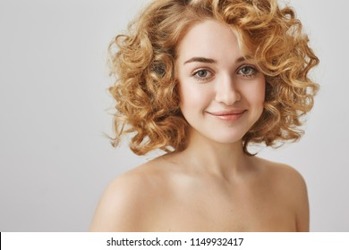 Body positive and beauty concept. Attractive european female student with blonde curly hair standing naked over gray background, smiling sensually at camera, expressing positive attitude.