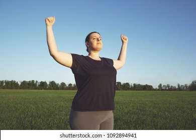 Body positive, freedom, high self esteem, confidence, happiness, success, inspiration. Overweight woman celebrating rising hands to the sky on summer meadow.