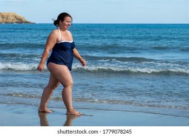 Cuerpo positivo. Mujer gorda feliz en la playa