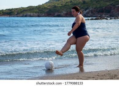 Cuerpo positivo. Feliz mujer gorda jugando al balón en la playa. El deporte para todos