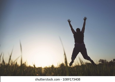Body positive, high self esteem, confidence, freedom, happiness, inspiration, obesity. Overweight woman jumping high at sunset sky background