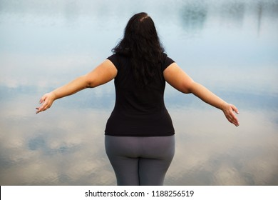 Body positive, high self esteem, confidence, freedom, obesity. Overweight woman rising hands expressing joy and happiness, view from the back
