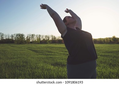 Body positive, obesity, wellness, outdoor activity and health. Young overweight woman practicing yoga at summer meadow.