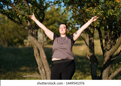 Body positive, success, freedom, happiness, confidence, self esteem. Overweight woman rising hands to the sky. Obesity and outdoor activity