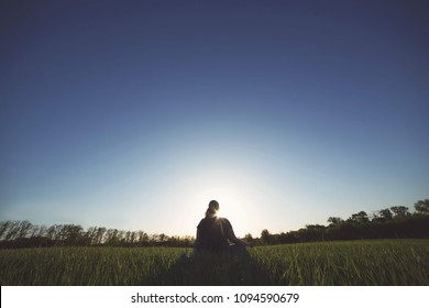 Body positive, tranquility, calm state of mind, meditation, relax. Overweight woman meditating sitting on summer meadow.