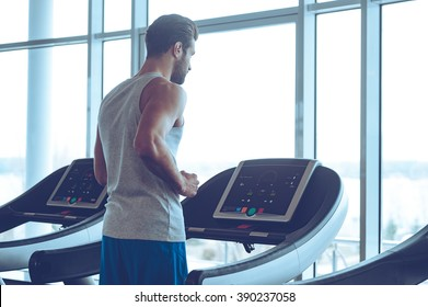 Body power. Young man in sportswear running on treadmill in front of window at gym