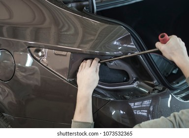 Body repair. The mechanic at the auto shop with tools to repair dents in car body