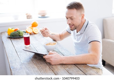 Body requirements. Attractive gay positive man holding spoon while trying granola and studying blog about biohacking