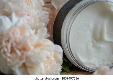 body scrub brown in a jar on a background of flowers