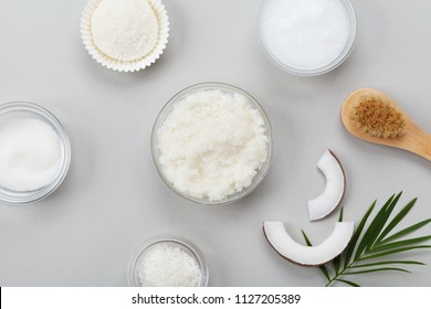 Body scrub of coconut oil, sugar and shavings in glass jar top view. Homemade cosmetic for peeling and spa care. Flat lay.